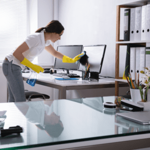 Employee disinfecting her personal workspace to help protect herself from the coronavirus at the office