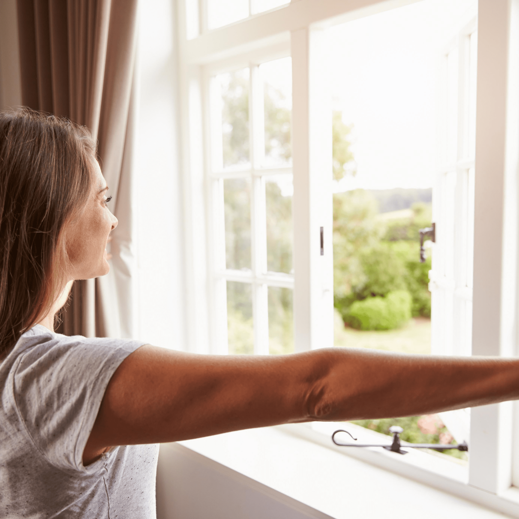 Woman opening window to improve indoor air quality in home office